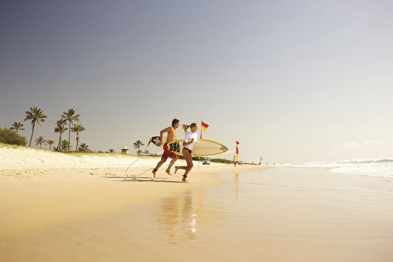 Mensen rennen strand surfboard