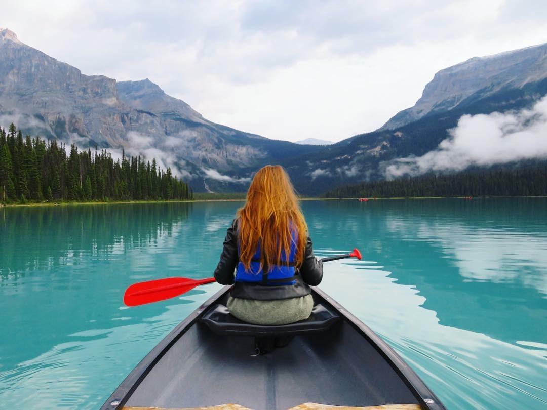 Meisje met rood haar gaat kano varen over het blauwe Emerald meer in de Canadese Rockies.