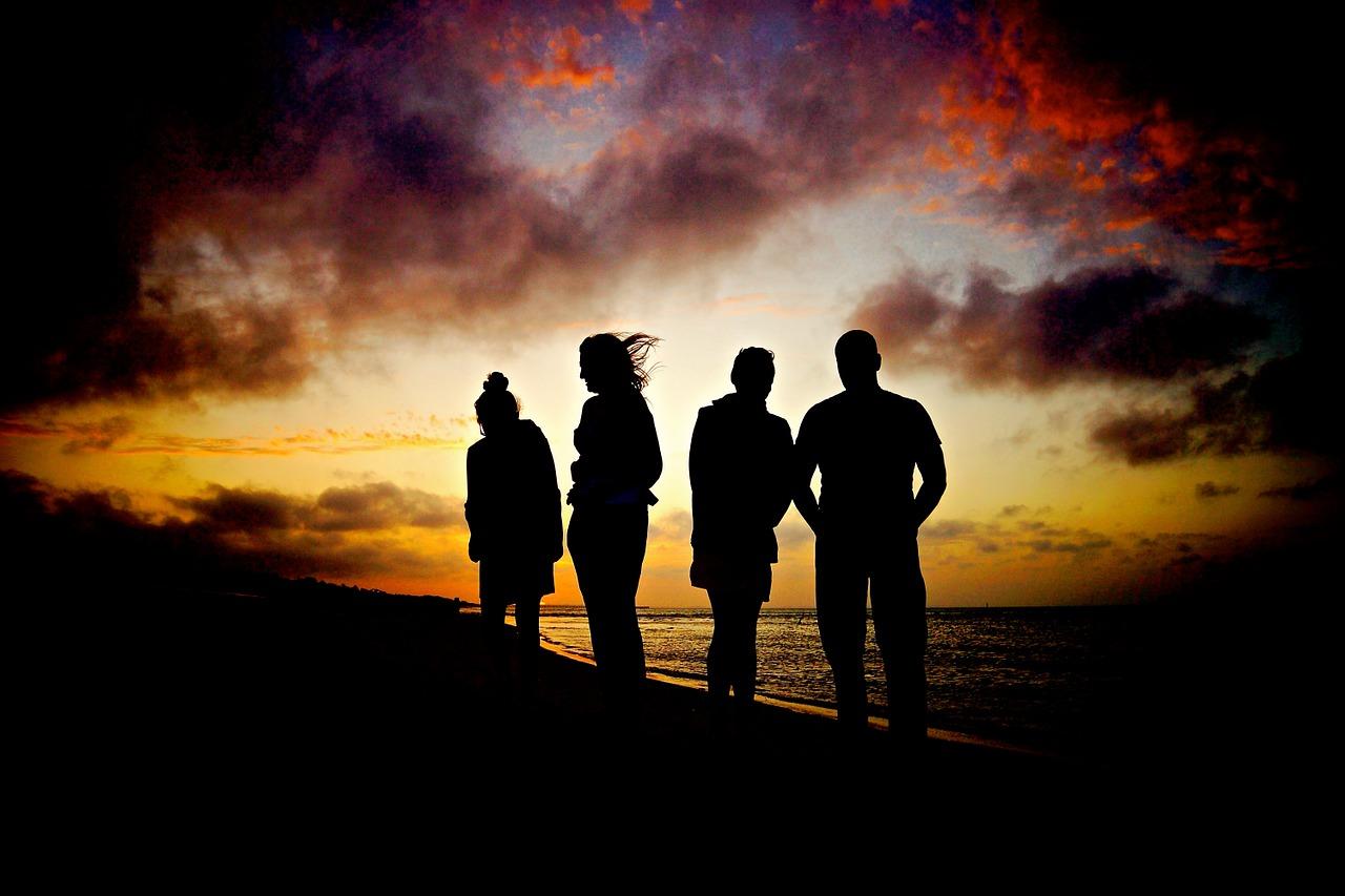 Vier personen op strand zonsondergang