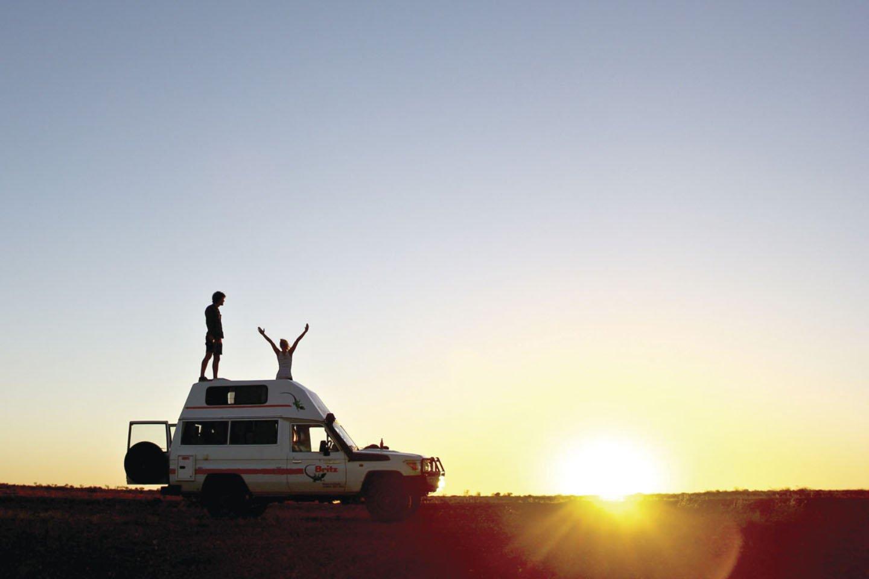 2 Backpacker auf ihrem 4WD im Sonnenuntergang