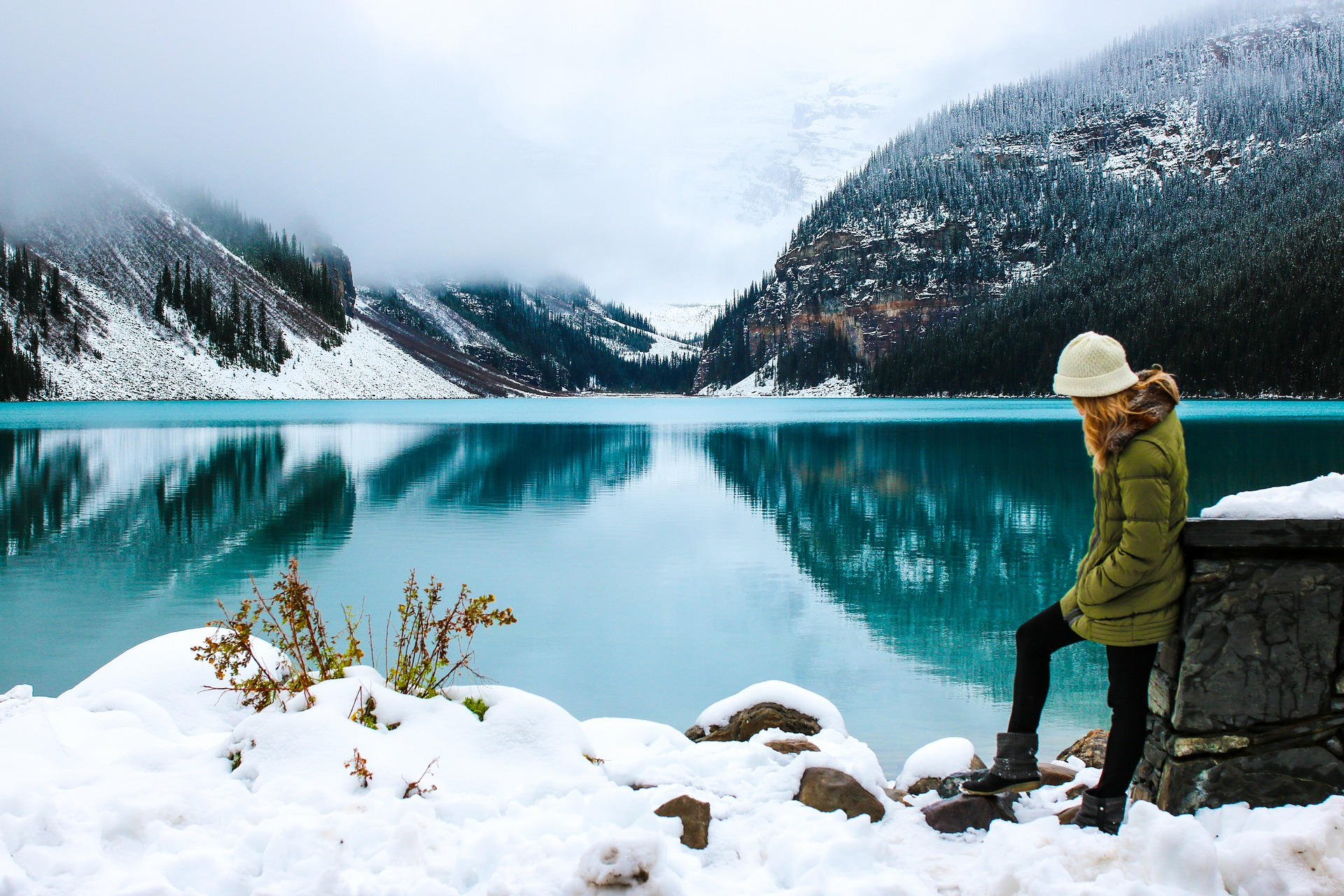 Meisje maakt winterwandeling bij blauw meer in de Canadese Rockies.
